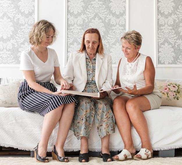 Frauen der multi generation, die auf sofa sitzen und altes gedächtnisalbum schauen Kostenlose Fotos