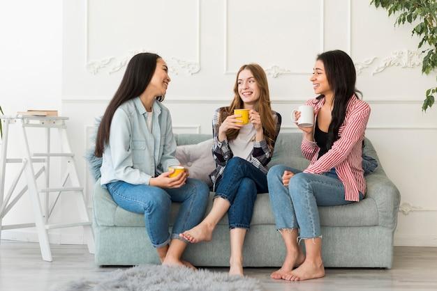 Frauen, die auf sofa sitzen und in der hand halten, cups halten Kostenlose Fotos