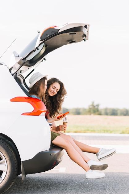 Frauen, die auf stamm des weißen autos sitzen Kostenlose Fotos