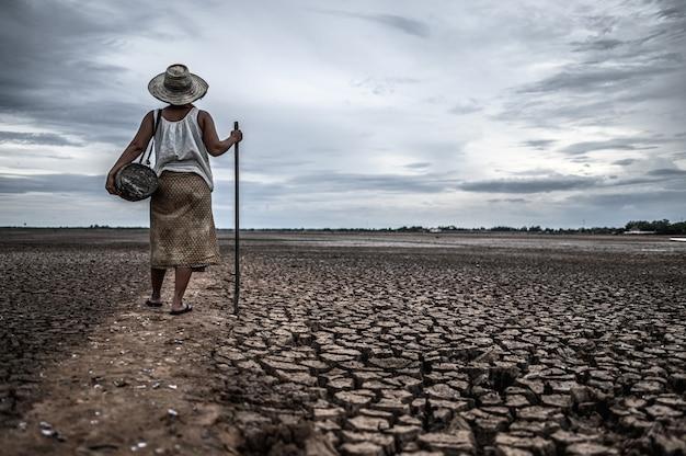 Frauen, die auf trockenem boden und fischereiausrüstung, globaler erwärmung und wasserkrise stehen Kostenlose Fotos