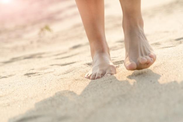 Frauen, die barfuß auf die weiße sandnatur auf dem strand gehen. sommerausflug Premium Fotos