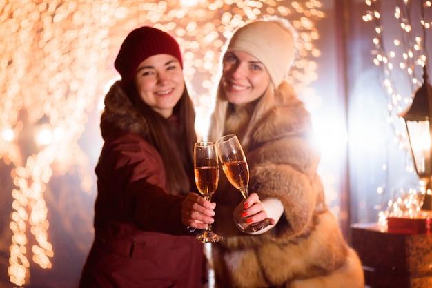 Frauen, die champagner genießen. outdoor-porträt von damen auf licht Premium Fotos