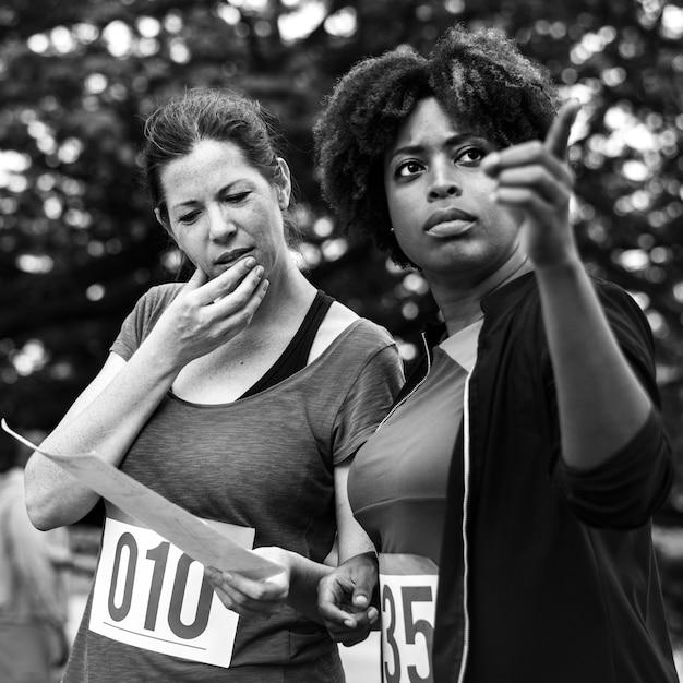 Frauen, die die karte für orienteering-kastenstandort betrachten Kostenlose Fotos