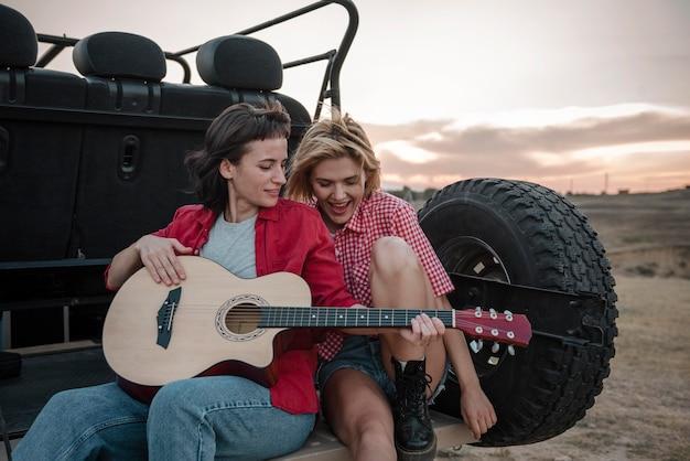 Frauen, die gitarre spielen, während sie mit dem auto reisen Kostenlose Fotos