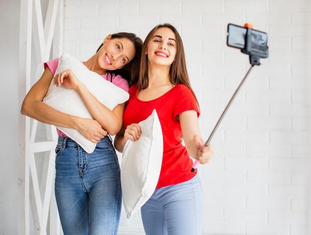 Frauen, die kissen halten und selfie nehmen Kostenlose Fotos