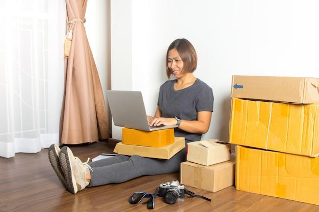 Frauen, die laptop-computer vom haus auf bretterboden bearbeiten Premium Fotos