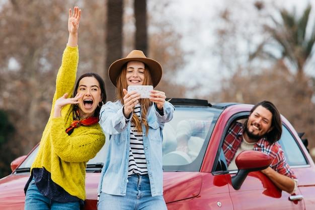 Frauen, die spaß haben und selfie auf smartphone nahe dem mann sich lehnen, der sich vom auto lehnt Kostenlose Fotos
