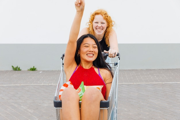 Frauen, die spaß mit einkaufswagen haben und kamera betrachten Kostenlose Fotos