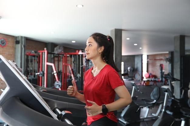 Frauen, die sportschuhe an der turnhalle während einer jungen kaukasischen frau laufen lassen Premium Fotos