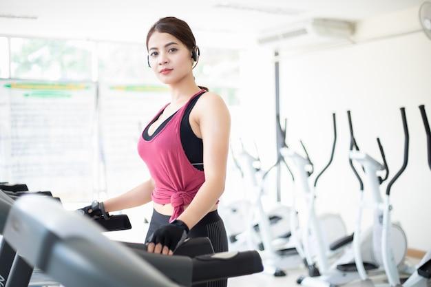 Frauen, die sportschuhe im fitnessstudio während einer jungen kaukasischen frau laufen lassen Premium Fotos