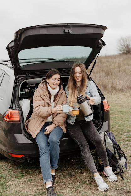 Frauen, die tee auf autoreisepause trinken Kostenlose Fotos