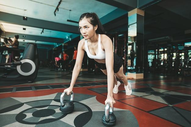 Frauen, die trainieren, indem sie den boden mit der kettlebell in der turnhalle drücken. Kostenlose Fotos