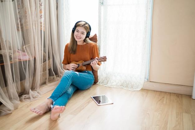 Frauen, die zu hause gitarre im wohnzimmer spielen Premium Fotos