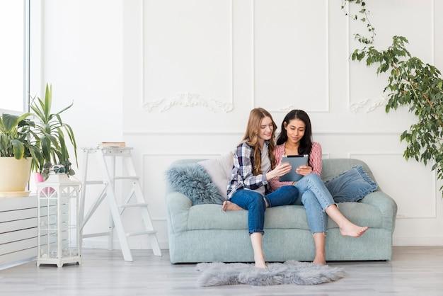 Frauen, die zusammen auf sofa sitzen und etwas in der tablette aufpassen Kostenlose Fotos