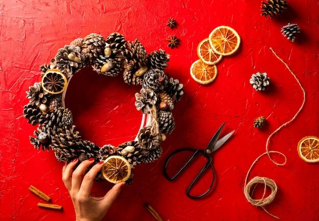 Frauen-hände, die weihnachtskranz halten Premium Fotos