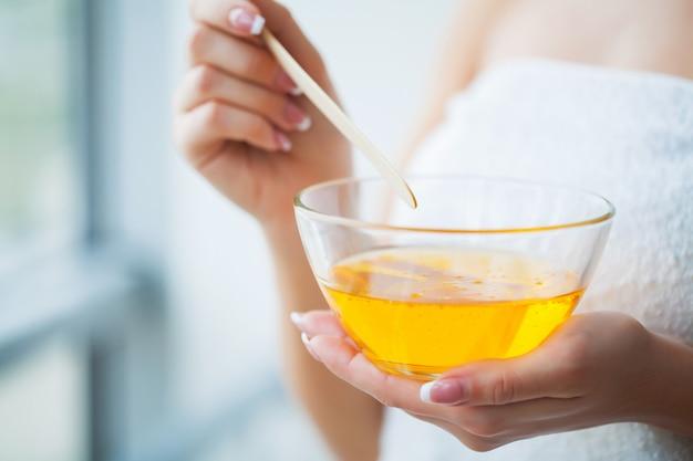 Frauen halten orange paraffinwachsschale. frau im schönheitssalon Premium Fotos