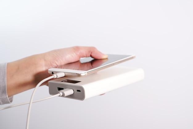 Frauen hand halten smartphone und ladegerät, powerbank und smartphone verbindet Premium Fotos