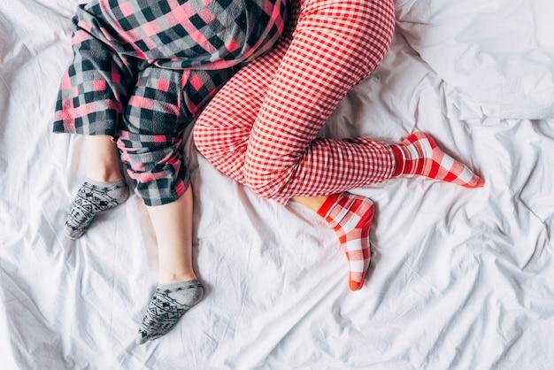 Frauen in farbigen pyjamas und socken schlafen auf dem bett Kostenlose Fotos