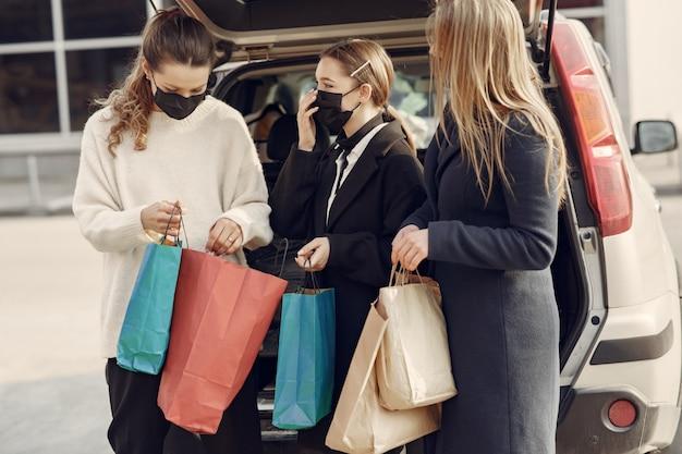 Frauen in masken gehen mit einkaufstüten nach draußen Kostenlose Fotos