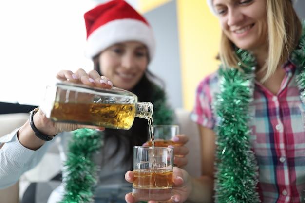 Frauen in roten weihnachtsmannhüten gießen alkohol mit eis in glas Premium Fotos