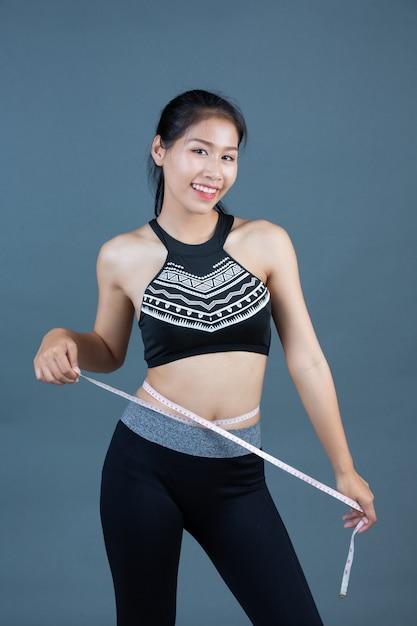 Frauen in sportbekleidung halten eine taille. Kostenlose Fotos