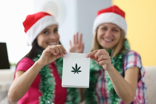 Frauen in weihnachtshüten halten eine tüte marihuana-blätter und winken Premium Fotos