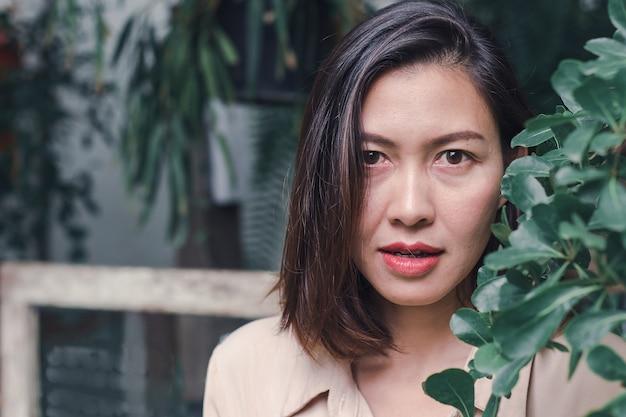 Frauen lächeln glücklich, wenn sie die blätter bewundern Premium Fotos