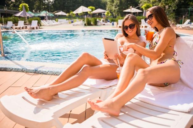 Frauen liegen auf chaiselongue und benutzen digitale tablets. Premium Fotos