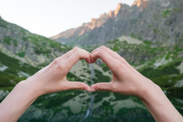 Frauen machen herzform mit ihren händen gegen die berge in der nähe des sees. Premium Fotos