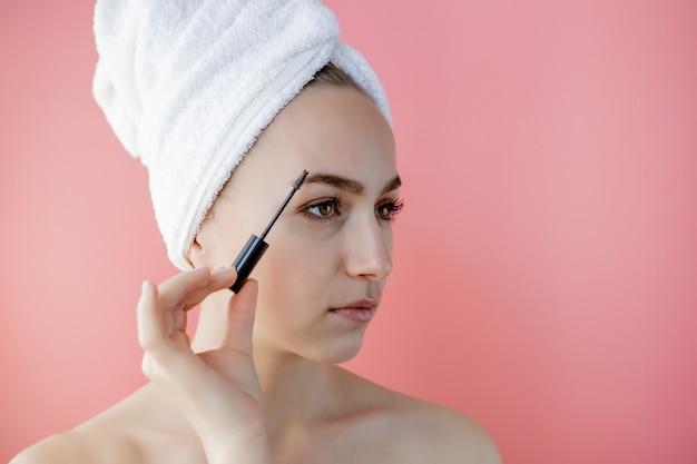 Frauen make-up. nahaufnahme des jungen weiblichen modellgesichtes mit glatter weicher gesunder haut und frischem make-up. schöne mädchenhand mit augenbrauen-gel-bürste für augenbrauen. schönheitswerkzeuge. hochauflösendes bild. Premium Fotos