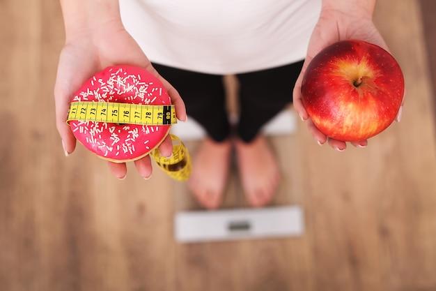 Frauen-messendes körpergewicht auf der waage, die donut und apfel hält. Premium Fotos
