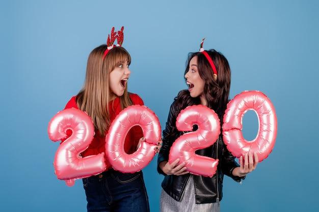 Frauen mit 2020 ballonen des neuen jahres, welche die lustigen weihnachtsbänder getrennt über blau tragen Premium Fotos