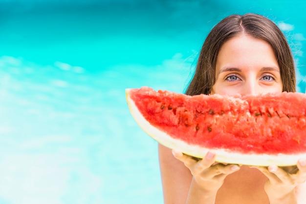 Frauen mit der wassermelone, die nahe swimmingpool steht Kostenlose Fotos