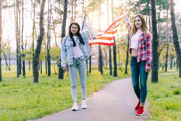 Frauen mit flagge von usa draußen gehend Kostenlose Fotos