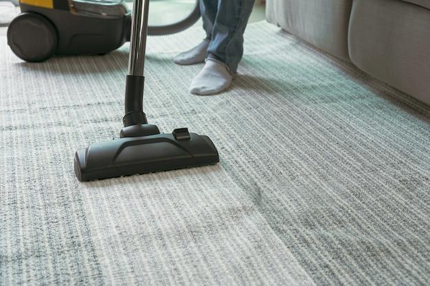 Frauen mit staubsauger reinigung teppich im wohnzimmer. Premium Fotos