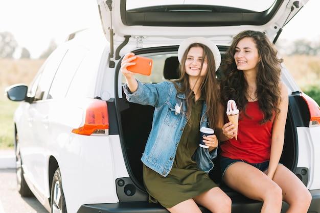 Frauen nehmen selfie am kofferraum Kostenlose Fotos