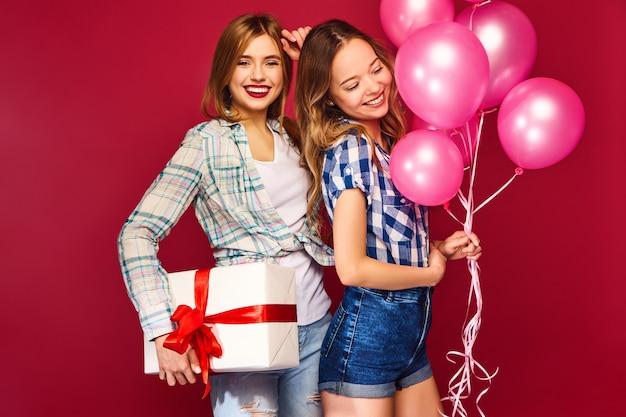Frauen posieren mit großer geschenkbox und rosa luftballons Kostenlose Fotos