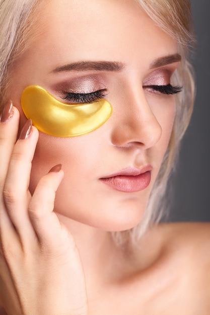 Frauen-schönheits-gesicht mit maske unter augen. schöne frau mit natürlichem make-up und goldkollagen-flecken. Premium Fotos