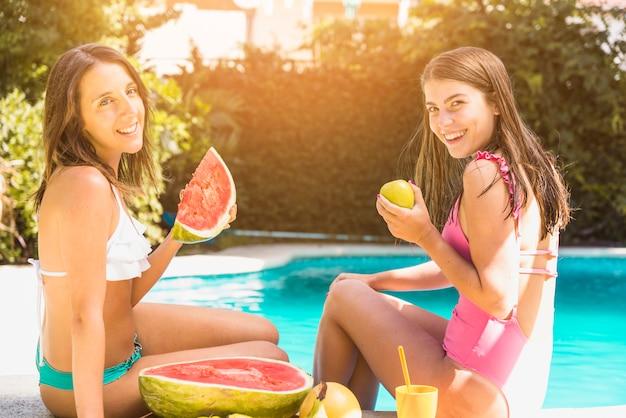 Frauen sitzen am rand des pools mit früchten Kostenlose Fotos