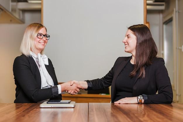 Frauen sitzen am tisch händeschütteln lächelnd Kostenlose Fotos
