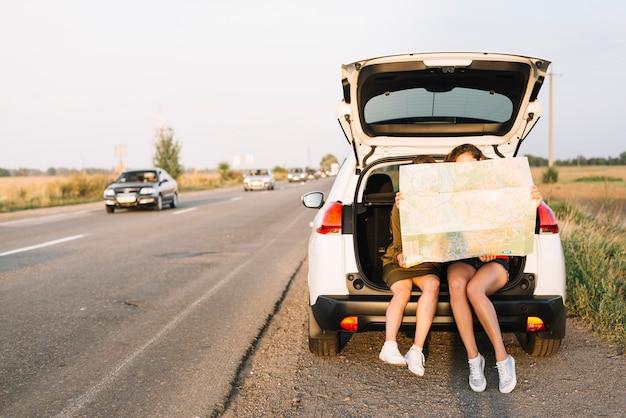 Frauen sitzen auf dem auto mit karte Kostenlose Fotos