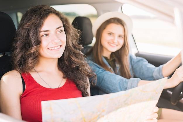 Frauen sitzen im auto mit karte Kostenlose Fotos