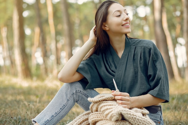 Frauen sitzen in einem sommerpark und stricken Kostenlose Fotos