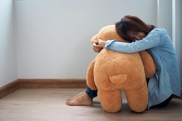 Frauen sitzen traurig und umarmen teddybären Premium Fotos