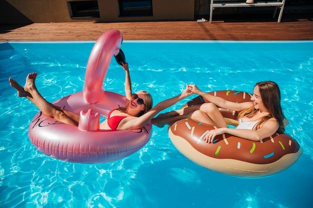 Frauen spielen im pool mit schwimmringen Kostenlose Fotos