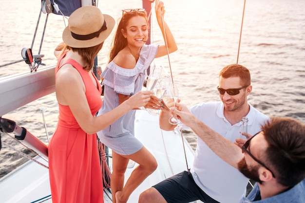 Frauen stehen vor männern. alle halten gläser champagner Premium Fotos
