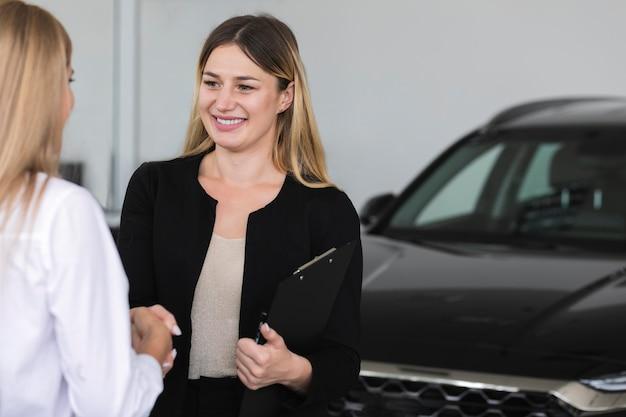 Frauen stellen sich im autosalon vor Kostenlose Fotos