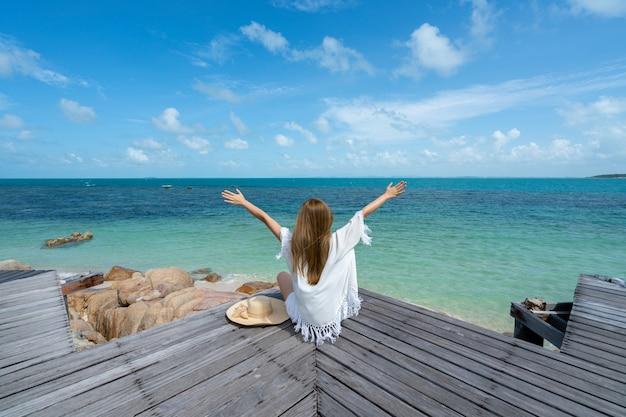 Frauen tragen einen seehut, den sie glücklich ist und auf der hölzernen brücke sitzt und zur strandküste schaut Premium Fotos
