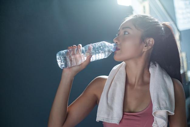 Frauen trinken nach dem training wasser aus flaschen und taschentüchern im fitnessstudio. Kostenlose Fotos