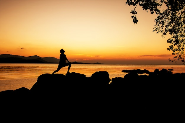 Frauen üben und entspannen sich auf strandsonnenunterganghintergrund Premium Fotos